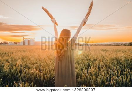 Woman Standing Golden Wheat Meadow With Brench Buguette. Say Yes To Bread. The Most Popular Kind Of