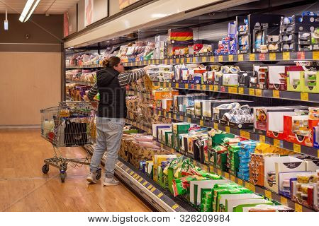 Sydney, Australia 08-06-2019 A Young Woman With Shopping Trolley Surveying Meat And Cheese Aisle At