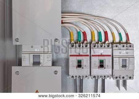 A Large Input Circuit Breaker And A Series Of Circuit Breakers With Cables Connected To Them. Each P