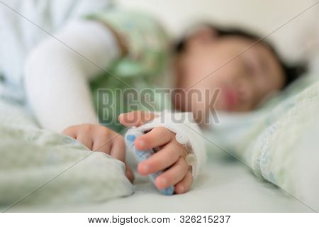 Little Asian Girl Was Lying Ill In Bed At The Hospital, Close-up Children Hand Intravenous Treat Wit