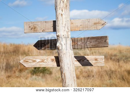 Rural Empty Wooden Guidepost With Arrow Shaped Planks Over Blue Sky And Summer Meadow Background