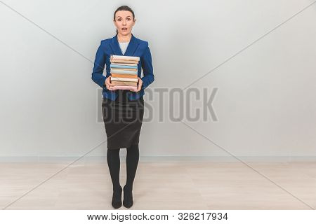 Lovely Female Teacher Holding A Stack Of Colorful Books, Looking At The Camra With Surprised Face Ex