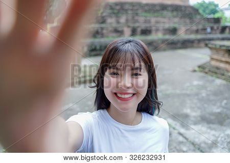 Young Asian Female Traveler Taking A Selfie While Traveling In Popular Tourist Attraction Thailand A