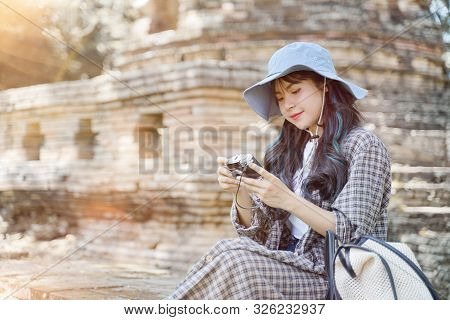 Beautiful Young Asian Female Traveler Taking A Photo With Retro Camera While Traveling In Popular To