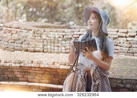 Beautiful Young Asian Female Traveler Writing On Notebook While Sightseeing In Popular Tourist Attra