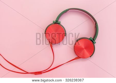 Red Headphones On Pink Background. Minimalist Simple Photo Of Earphones With Copy Space. Red Dj Head