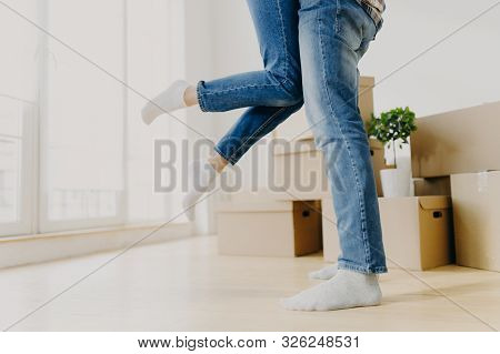 Happy Unknown Couple Move In New Abode, Man Lifts Woman, Wear Jeans, Pose In Empty Room With Carton