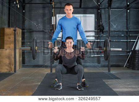 Personal Trainer Helps Woman Work With Barbell At Squat Exercises In Gym. Front View.