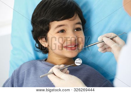 Little Arab Boy Sitting At Dental Chair With Open Mouth During Oral Check Up While Doctor. Visiting