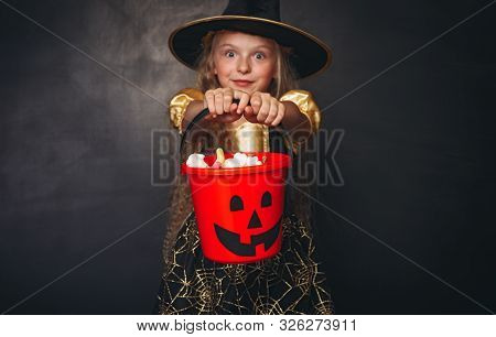 Shocked pretty girl in Halloween costume holding full candy collector in outstretched hands and looking at camera on black background poster