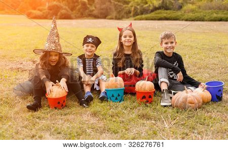 Happy children in Halloween costumes sitting on grass with pumpkins and candy collectors and looking at camera in autumn on nature background poster