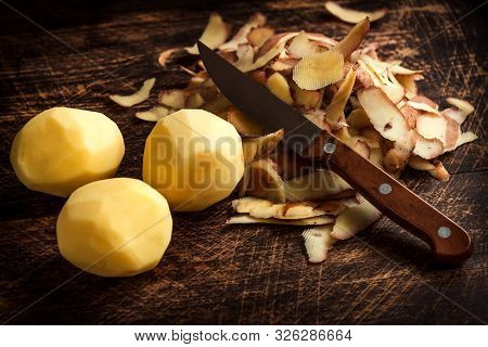 Peeling Potatoes. Peel Raw Potatoes And Potatoes On An Old Wooden Board And Knife.