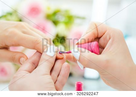 Experienced nail technician applying nail color to fingernails poster