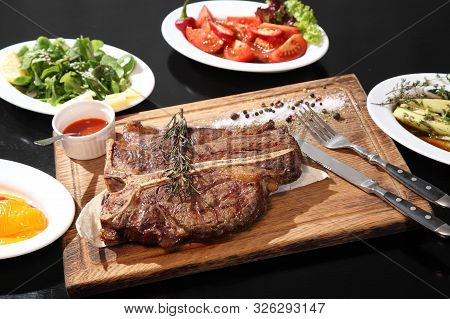 Beef Steak On Wooden Plate. Medium-roasted Steak Cut Into Pieces On A Wooden Board With Sauce And Se
