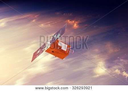 Space Satellite Flying In Orbit Over Sunset Clouds Orbiting Earth. Bright Light From The Sun And Gla