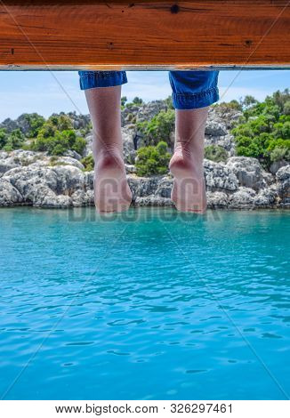 Bare Feet Hanging From A Wooden Pier Over Sea Water. Holiday Vacation By The Sea.