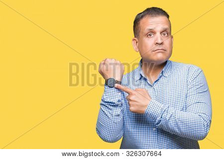 Middle age arab business man over isolated background In hurry pointing to watch time, impatience, upset and angry for deadline delay
