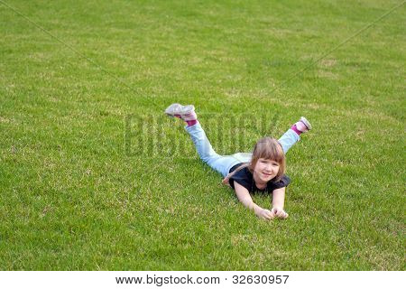 Young Smiling Girl Lying On A Lawn