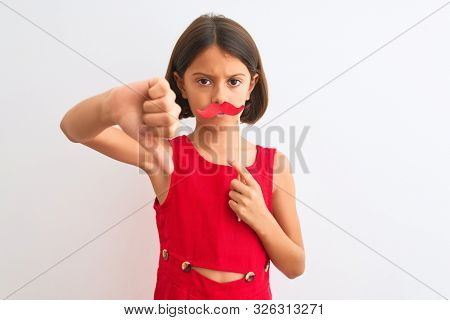 Beautiful child girl holding fanny party mustache standing over isolated white background with angry face, negative sign showing dislike with thumbs down, rejection concept