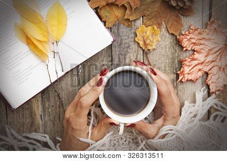 Hot Coffee In The Hands Of A Girl, A Book With Poems, Autumn Leaves, A Knitted Sweater On A Wooden T