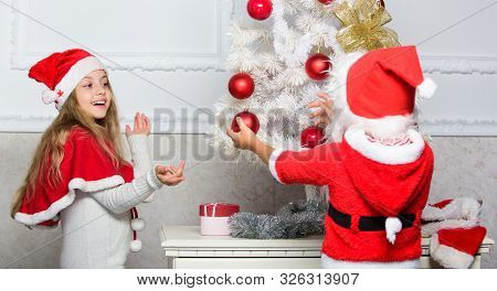 Family tradition concept. Children decorating christmas tree together. Siblings busy decorating. Boy and girl decorating tree. Cherished holiday activity. Kids in santa hats decorating christmas tree poster