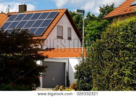 Solar Panels On The Tiled Roof Of A Building On A Bright Sunny Day. The Concept Of A Good Investment