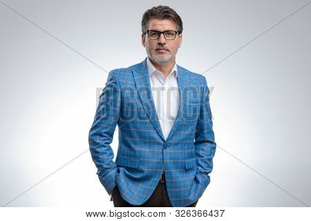 portrait of a sexy formal business man wearing a light blue suit and eyeglasses standing with hands in pockets and looking at camera serious against gray studio background