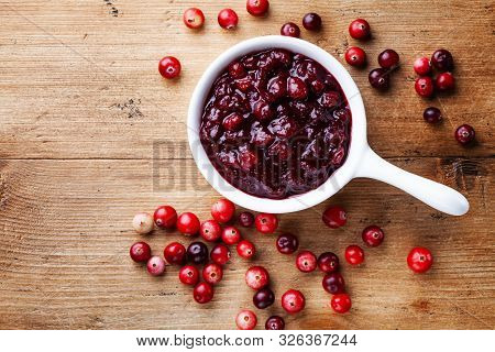 Cranberry Sauce In Ceramic Saucepan With Berries On Wooden Kitchen Table From Above.