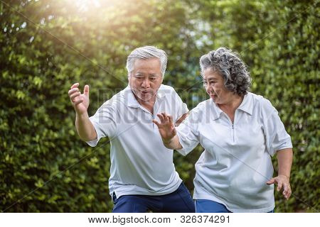Asian Couple In White Shirts Practicing Exercising At The Park. Good Health, Wellness. Senior Man Co
