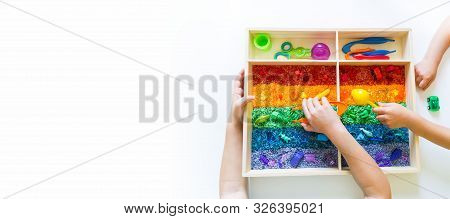 Sensory Box With Rainbow Rice Inside. Montessori Material Baby Copy Space