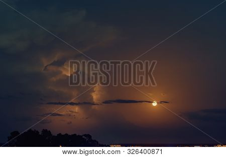 Picturesque Bright Blue, Grey And Orange Colours Cloudy Sky With Full Moon And Lighting During Mucky