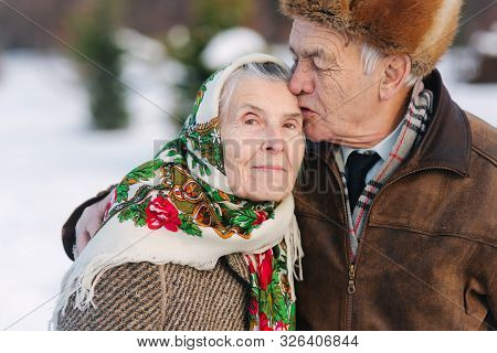 Portrait Of Senior Couple. Elderly Man Kiss His Wife In Weighty. Old Couple Walking In The Park In W