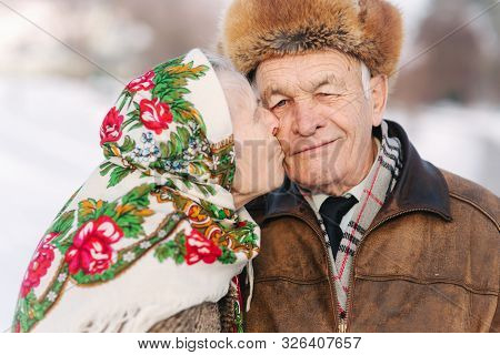 Portrait Of Happy Senior Couple. Elderly Woman Kiss Her Husband In Weighty. Old Couple Walking In Th