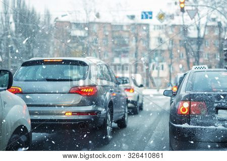 Many Cars Standing In Row On Traffic Lights During Snowfall In Cold Winter Morning. Traffic Jam On C