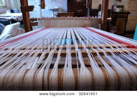 Wooden loom with strings of cloth