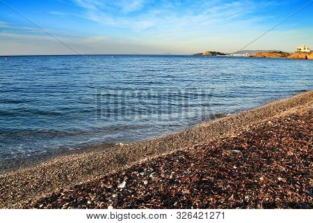 Beautiful beach with boulders, cliffs and mountains in Isla Plana village in Cartagena, Murcia, Spain in a sunny day poster
