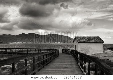 Wooden boardwalk along the beach in a stormy day in Isla Plana village in Cartagena, Murcia, Spain poster