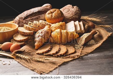 Different Kinds Of Bread With Nutrition Whole Grains On Wooden Background. Food And Bakery In Kitche