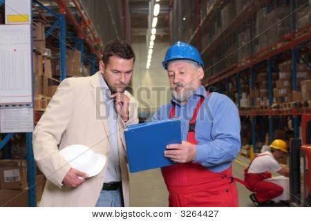 Manager And Senior Worker Reading Papers In Warehouse