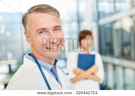 Smiling man as a senior physician with competence and success in the hospital