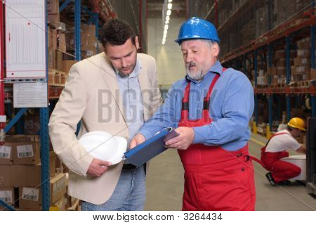 Manager And Older Worker In Warehouse