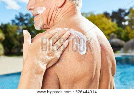 Woman rubs a man's back with sunscreen as sunscreen