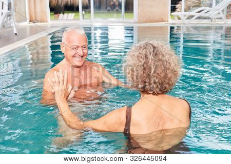 Senior couple has fun together while swimming in the pool of hotel spa