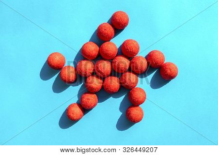 Star made of red sugary candies on turquoise background. poster