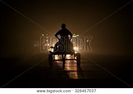 Tajikistan. 08/06/2019. A Peasant On A Cart Driven By A Donkey Rides At Night Along The Highway In T