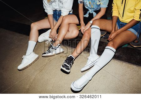 Cropped image of hipster multinational girls in streetwear sitting on skateboards at night party outdoors
