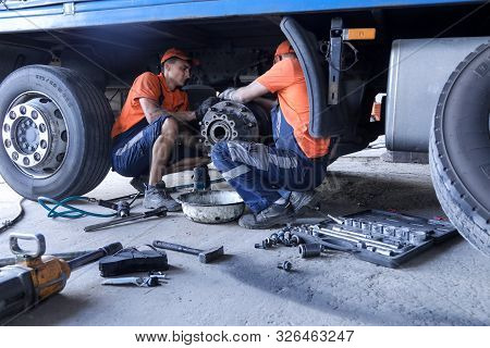 Two Mechanic Repairs A Truck. Replace Brake Disc And Pads