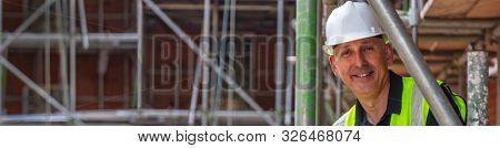 Panoramic web banner smiling male builder foreman, construction worker, engineer, surveyor, manager architect, wearing white hard hat and hi vis vest standing on scaffolding on building site panorama