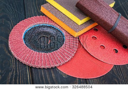 Set of abrasive tools and sandpaper on black vintage wooden background wizard is used for grinding items poster