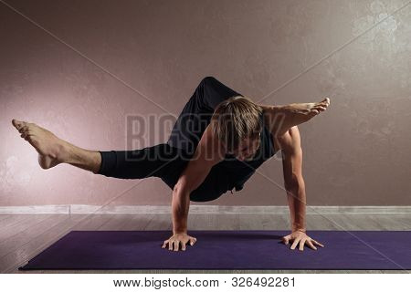 Young Sporty Man Practicing Yoga, Meditating In Half Lotus Pose, Working Out, Wearing Sportswear, In
